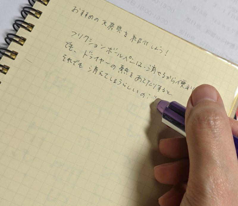 画像:M先生のおすすめのペン② ノートには、「おすすめの文房具を紹介しよう! フリクションボールペンは消せるから便利。でも、ドライヤーの熱をあてたりするとそれでも消えてしまうらしいのだ」と書かれている。
